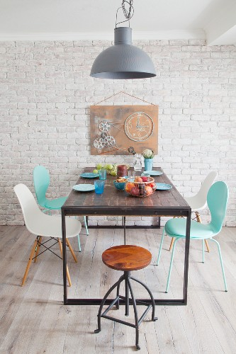 Classic chairs around table and hand-made artwork with cogs on wall