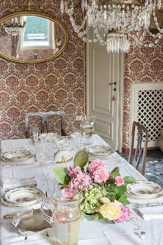 Flower arrangement on festively set table in dining room