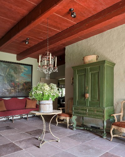 Green-painted Swedish cupboard and table under French 19th-century glass chandelier