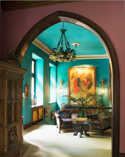Armchairs and coffee table on landing below oil painting on turquoise wall