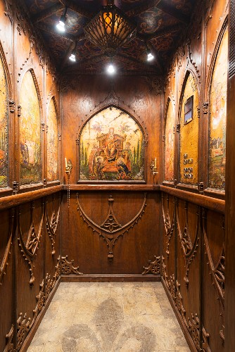 Wood-panelled elevator with coffered ceiling and biblical imagery