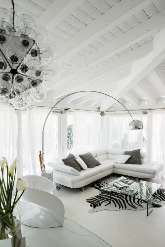White couch, arc lamp and zebra-skin rug in elegant living area