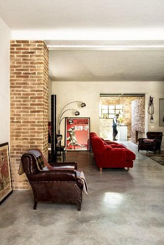 Leather armchair and red couch in living area with view into open-plan kitchen