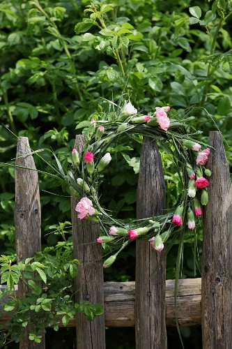 Wreath of carnations hung on wooden fence