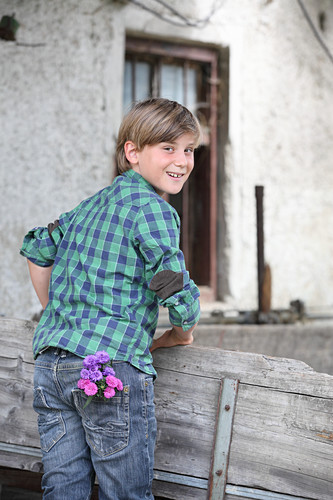 Boy with asters in trouser pocket