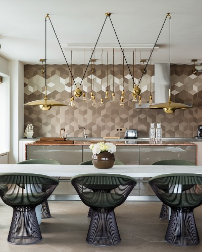 Retro metal chairs at white table and geometric wall tiles in elegant, open-plan kitchen