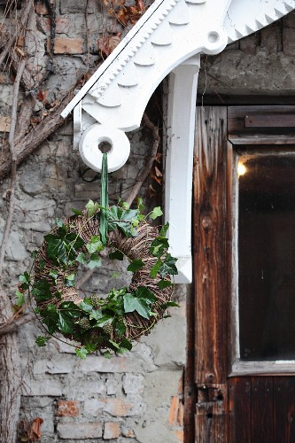 Wreath of willow and green ivy tendrils hung from white porch roof