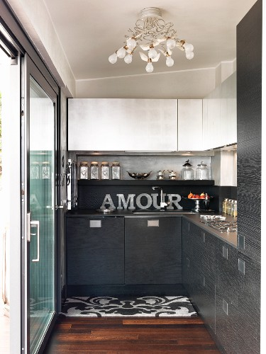 Black fitted kitchen with white wall units and sliding terrace doors