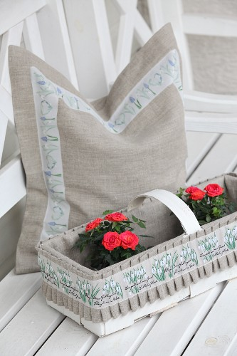 Cushion cover hand made from undyed linen with floral trim behind roses in decorated chip wood basket