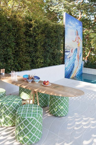 Surfboard table with green poufs in front of pool and mosaic