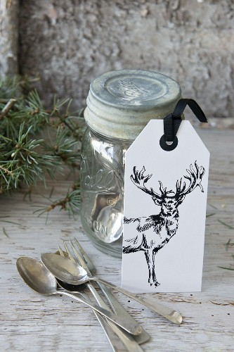 Gift tag with picture of stag leaning against preserving jar holding silver cutlery