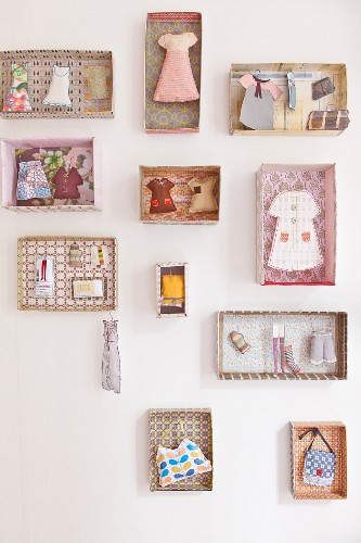 Miniature items of clothing and feminine accessories in separate patterned cardboard boxes
