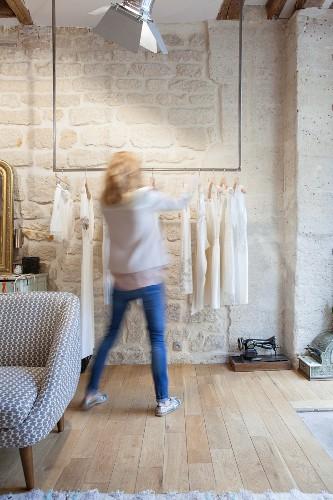 Frau an hängender Kleiderstange vor einer Natursteinwand