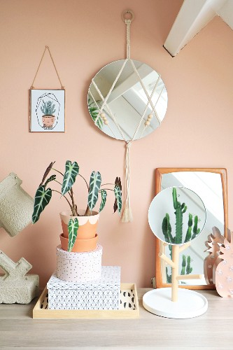 Mirror decorated with macramé and wooden beads on apricot wall above houseplant