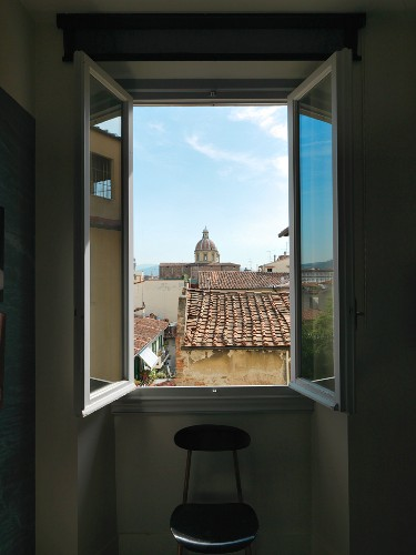 View through open window over the rooftops of Florence