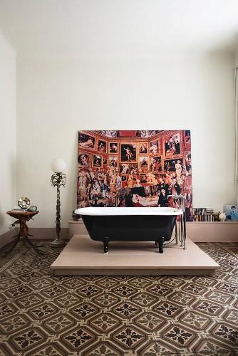 Free-standing bathtub on platform on patterned tiled floor