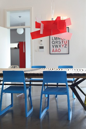 Red designer lamp above dining table and blue chairs