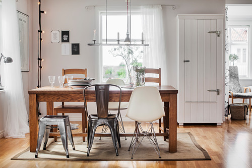 Various chairs around wooden table in bright dining room