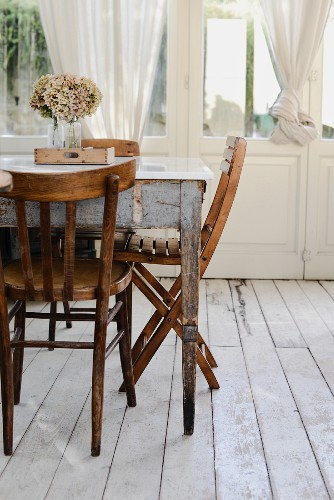 Vintage dining table and wooden chairs on wooden floor