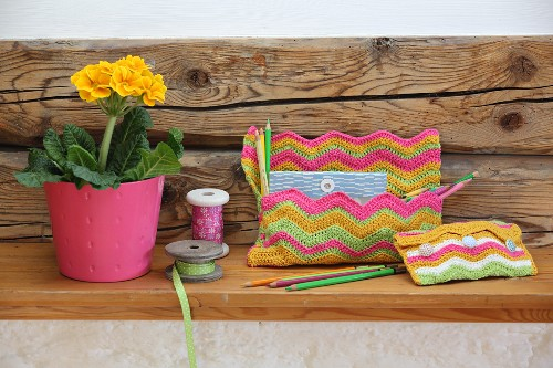 Two crocheted bags with colourful zigzag patterns