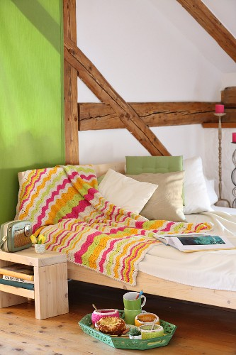 Crocheted blanket with zigzag pattern draped over bed in half-timbered room