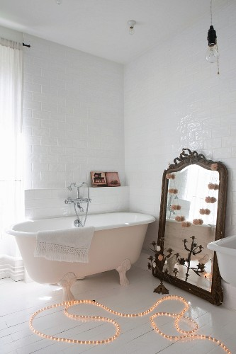 Rope light on floor next to free-standing bathtub and large mirror leant against wall in bathroom