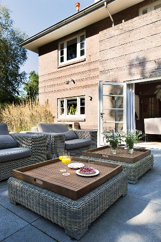 Lounge armchairs and tray tables on terrace outside brick house