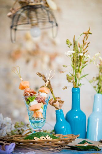 Melon skewers in glass on table set in summery style