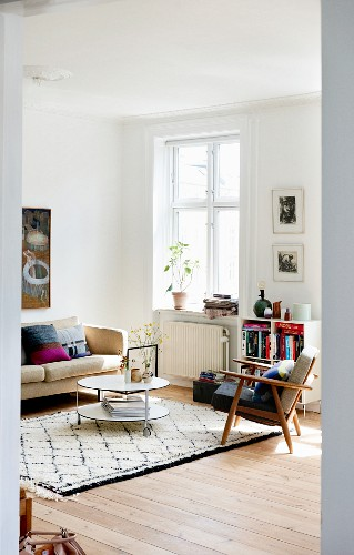 Armchair, coffee table and sofa in bright living room of period building