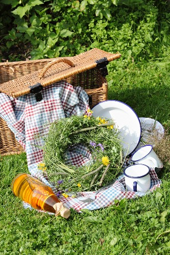 Picnic basket, blanket, enamel crockery and wreath of wildflowers on green lawn