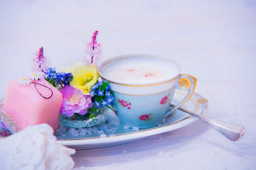 Cup of cappuccino, flower arrangement and petit four
