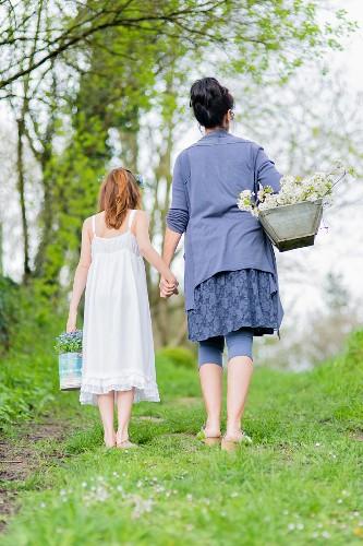 Mutter und Tochter Hand in Hand auf einer Frühlingswiese mit Blumenernte