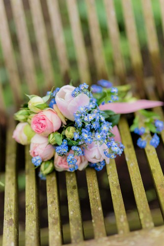 Strauß mit Rosen, Tulpen und Vergissmeinnicht auf dem Gartenstuhl