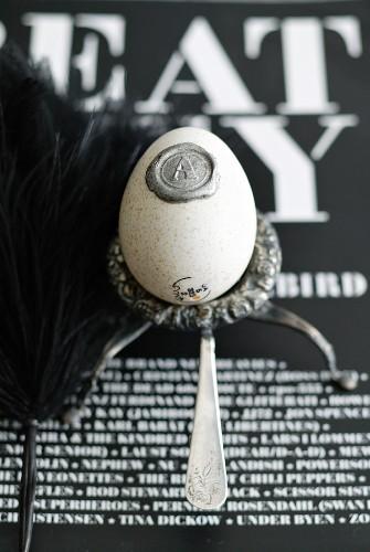 Ausgeblasenes Hühnerei mit Siegel auf Silbergefäß und schwarzweiß beschriftetem Hintergrund
