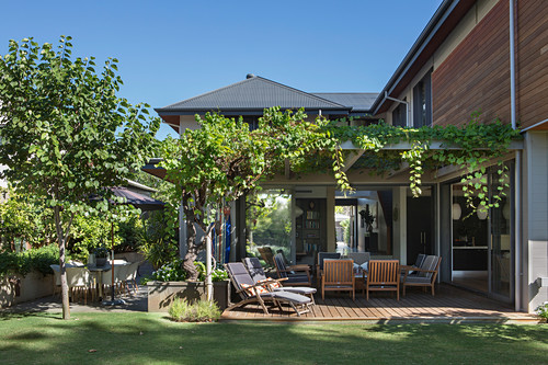 View from the garden onto the pergola with seating, overgrown with wine