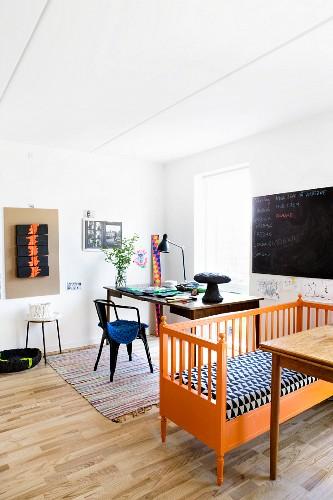 Alte orangefarbene Bank mit Musterpolster vor dem Schreibtisch