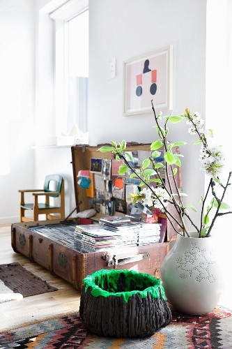 Lava-effect bowl and vase of twigs in front of CD collection in old suitcase