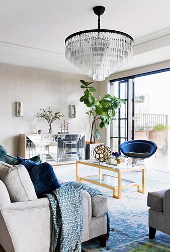 Chandelier in the elegant living room with an open patio door