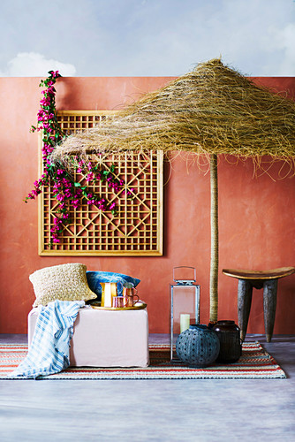 Oriental seat under the parasol against a red wall