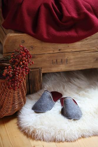 Grey felt slippers on white sheepskin rug under rustic wooden bed