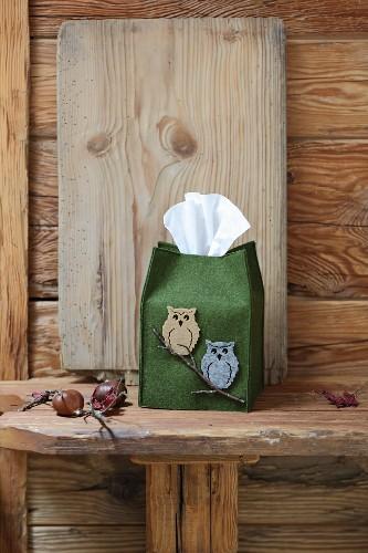 Decorative green felt tissue dispenser with owl motifs on rustic wooden bench