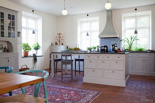 Island counter with breakfast bar in bright country-house kitchen