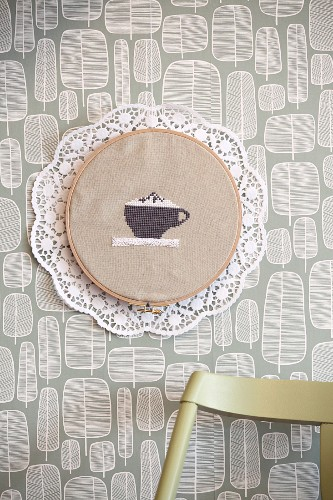 Hand-made wall decoration: coffee cup embroidered on cloth with lace trim and paper doily