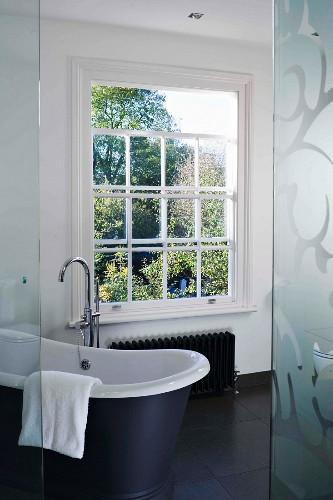 Lattice window and free-standing bathtub on black floor tiles