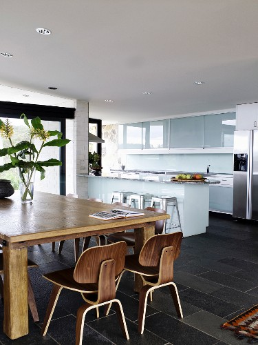 Wooden table and classic chairs in open-plan kitchen-dining room