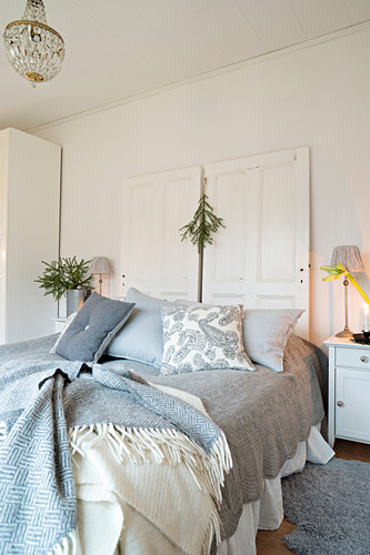 Old panelled doors used as headboard of bed with many blankets