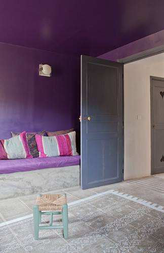 Rug painted on floor in front of masonry couch in living room with purple wall and ceiling