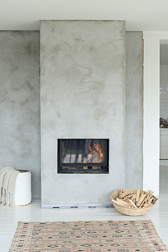 Basket of firewood next to fireplace in concrete wall