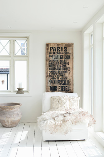 Fur blanket and knitted cushion on white récamier below vintage poster on wall