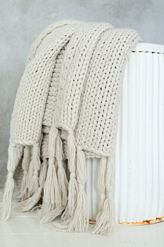 Pale knitted blanket in white metal bin